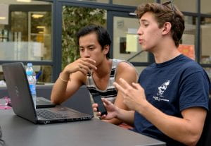 Two male students discuss a video they are viewing on a laptop.