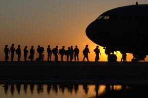 soldiers boarding aircraft in a line