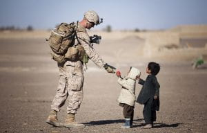 soldier handing something to two little kids