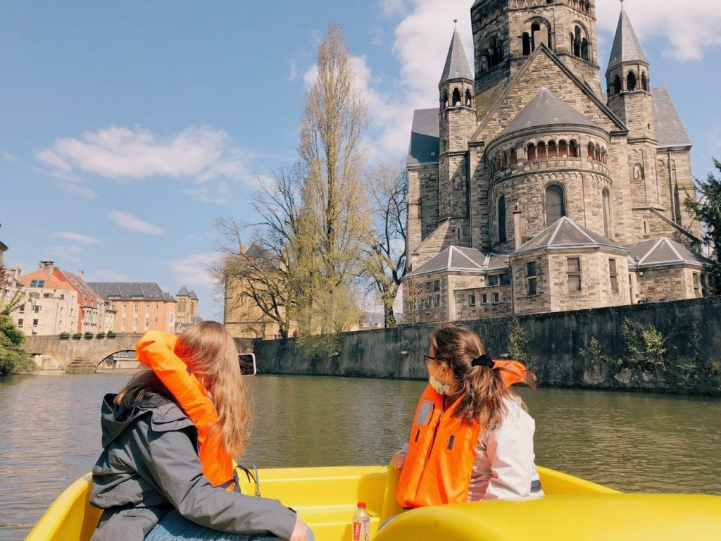 An image of Kaitlyn and another friend sitting in a bright yellow paddle boat on the river. Their backs are to the camera and they are looking to the right at the Temple Neuf from the water.