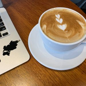 Wooden table with a light brown latte in a white mug on a white plate. The latte art is 3 white hearts in a vertical line. To the left of the mug is the corner of a silver laptop keyboard with a half peeled off sticker of Eurasia and Africa.