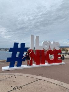 """ID: A woman with a maroon top and black shorts, spreading her arms in front of a large blue, white, and red sign that reads: """"#ILoveNice."""" Behind the sign, the sea and coastline is visible, and the sky is overcast."""