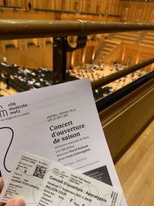 """An image of the concert programs in front of the seats in the concert hall. The text reads """"Concert d'ouverature de saison"""" which translates to the opening concert of the season."""