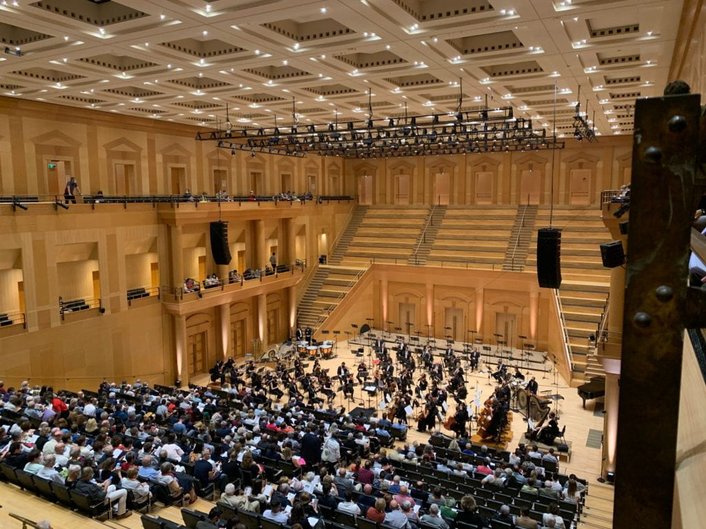 An image of the concert hall with rows of people sitting down.