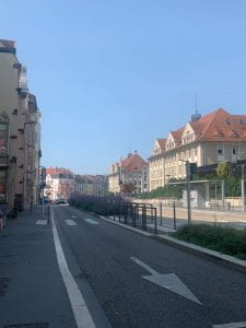 Road lined with pale colored buildings with red brick roofs. In the median of the road are purple flowers. The sky is a pale blue with no clouds.