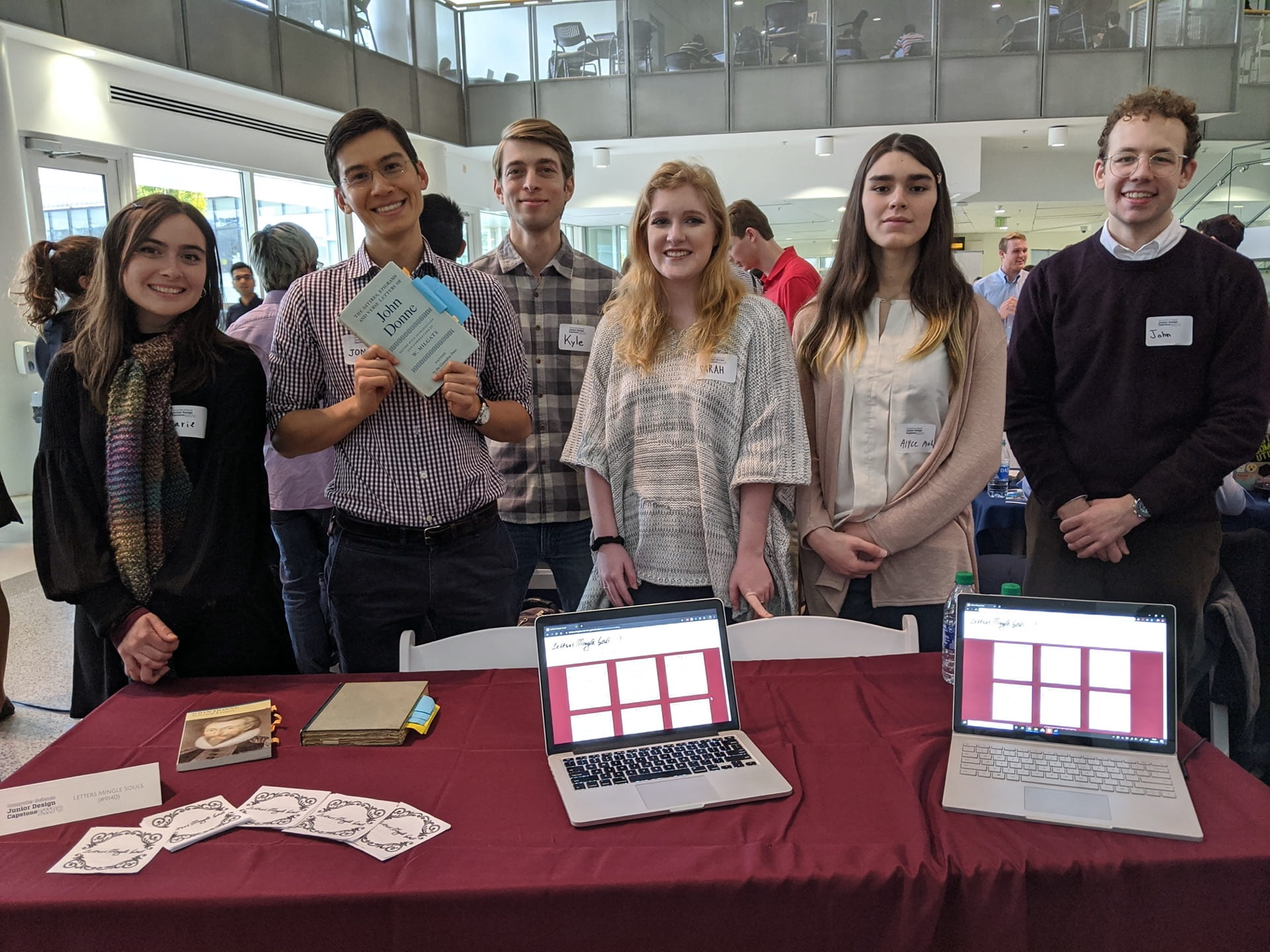 Students standing in front of table with computers ad paper at an academic expo