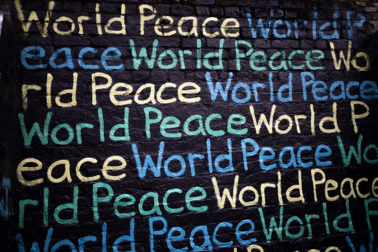 """The words """"World Peace"""" repeated in many different colors on a black wall"""